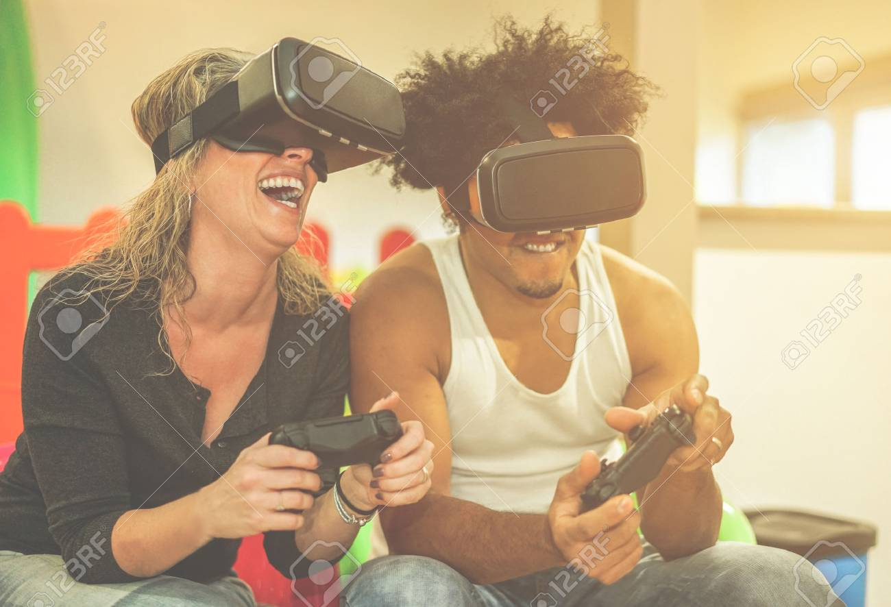 Happy multi ethnic couple playing video games virtual reality