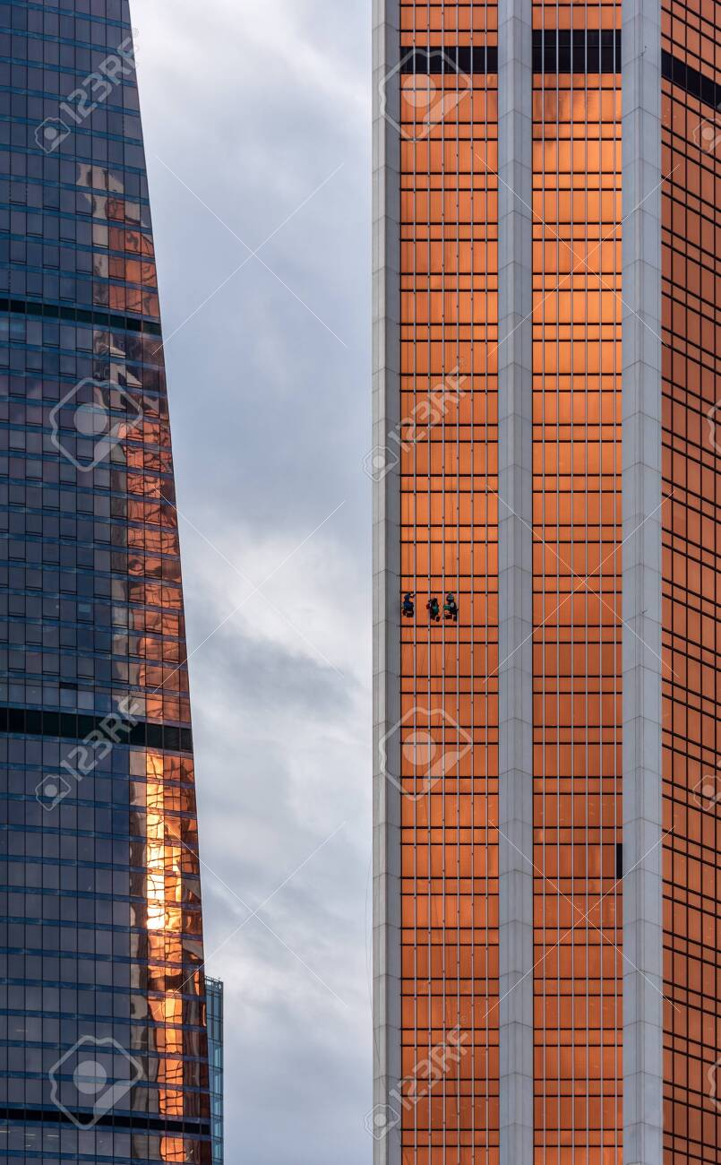 Window cleaners working at height on the glass facade of a skyscraper - 138037189