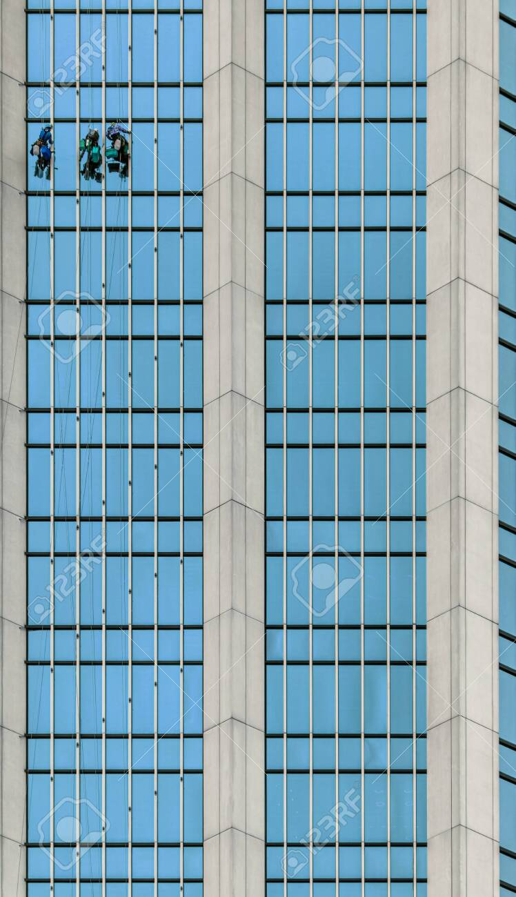 Window washers working at height on the glass facade of a skyscraper - 138036553