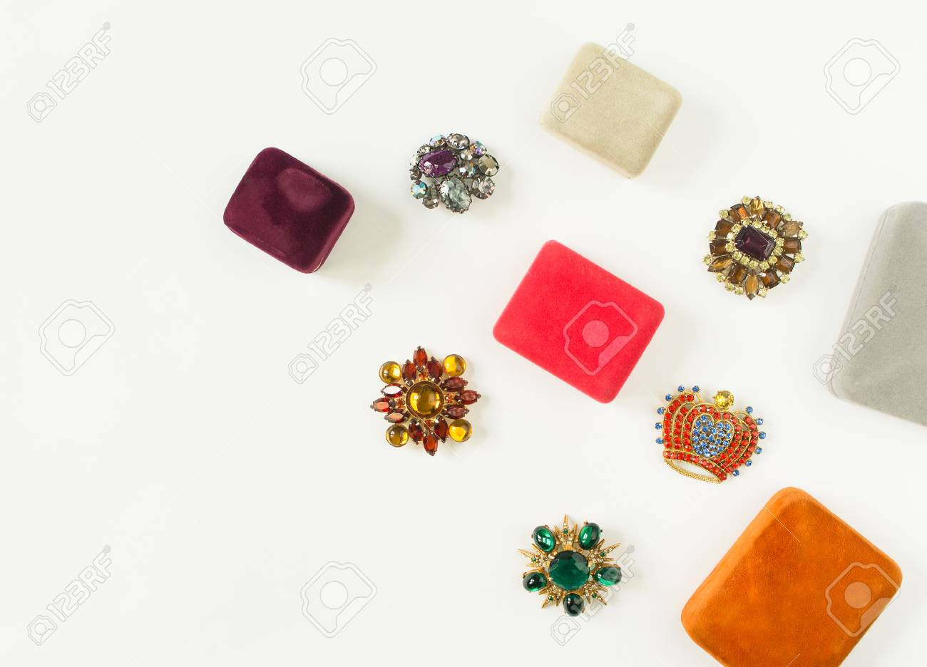 Stock Photo - Woman's Jewelry. Vintage jewelry background. Beautiful bright  rhinestone brooches and jewelry boxes on white background.