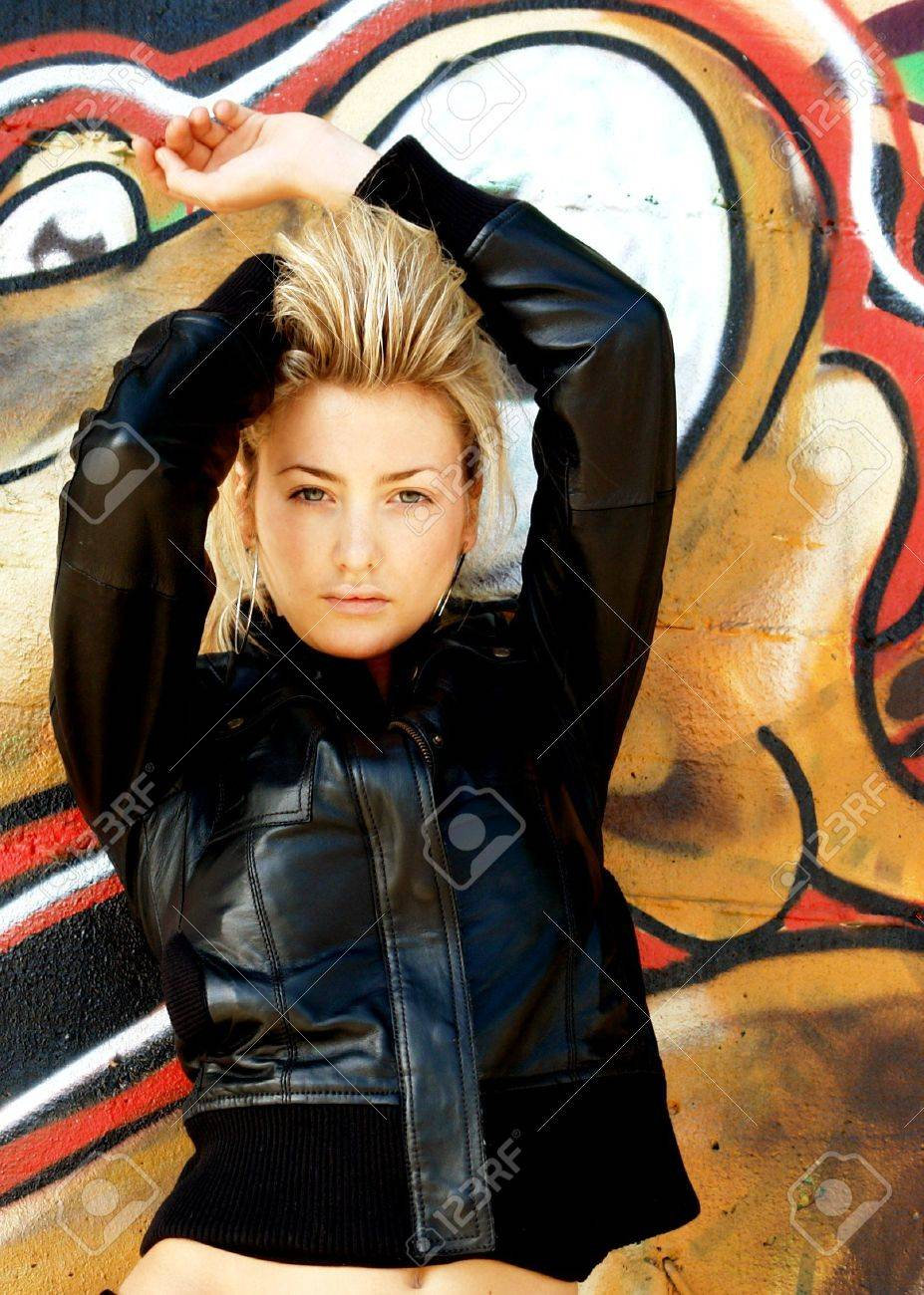 Blond punk girl with a leather jacked and high heels in front of a grafitti wall Stock Photo - 2601315