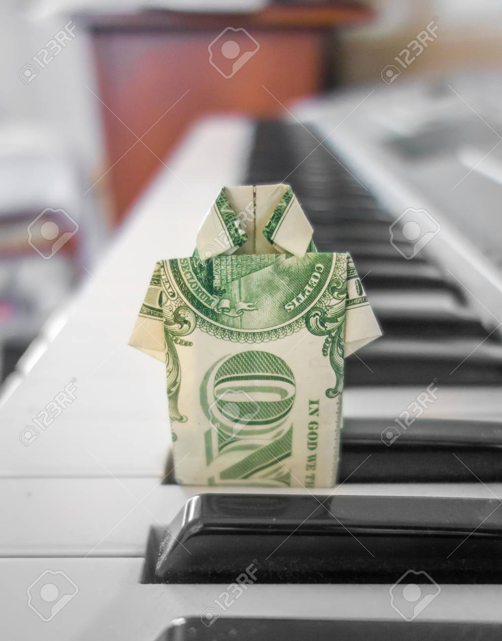 A Crisp Us Dollar Bill Folded Into Collared Shirt Origami Standing