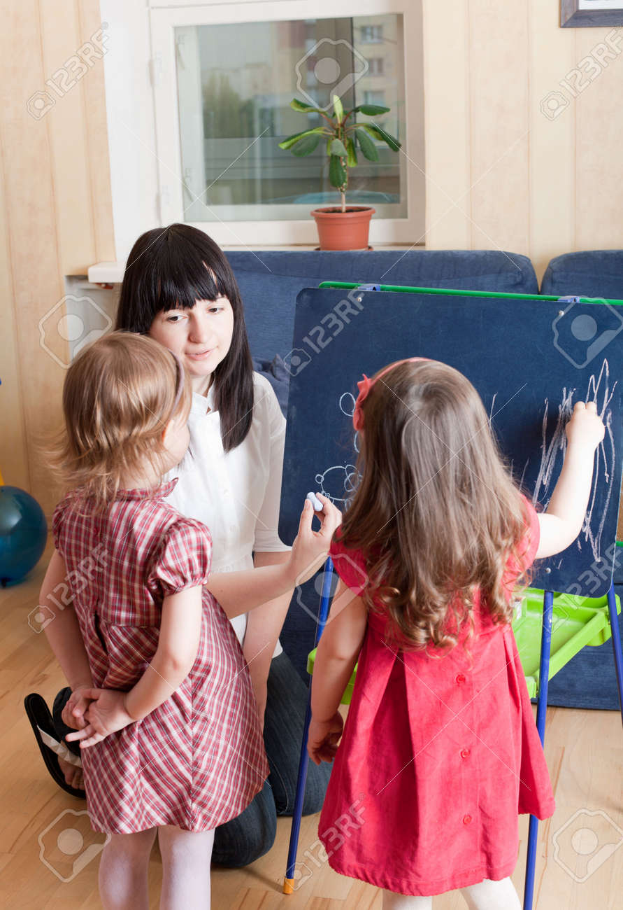 Mother teaching her daughters by drawing sketches on blackboard. Prepare to school series. Stock Photo - 4784236