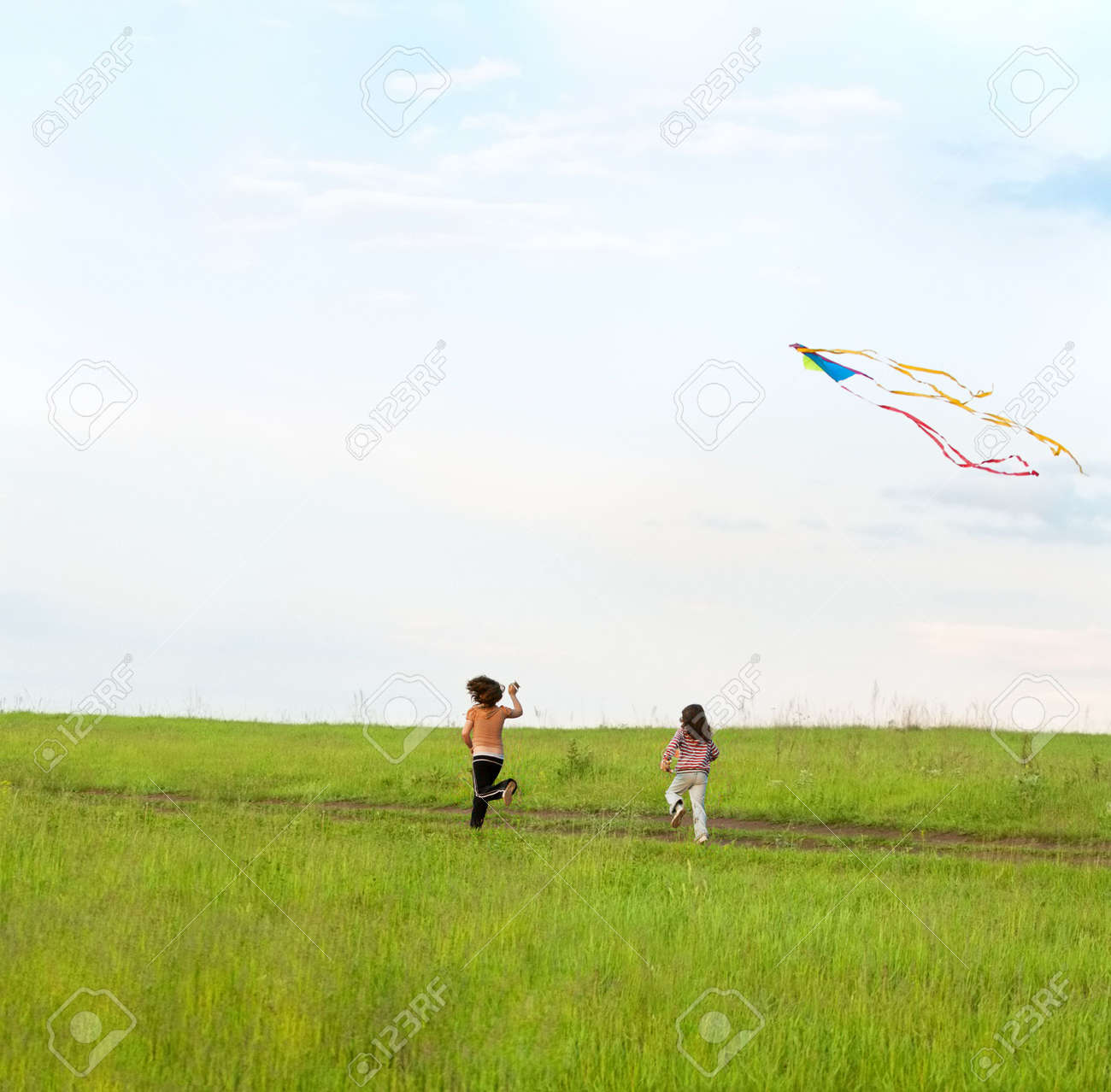 Two little girls running on a meadow and fly a kite Stock Photo - 5164399
