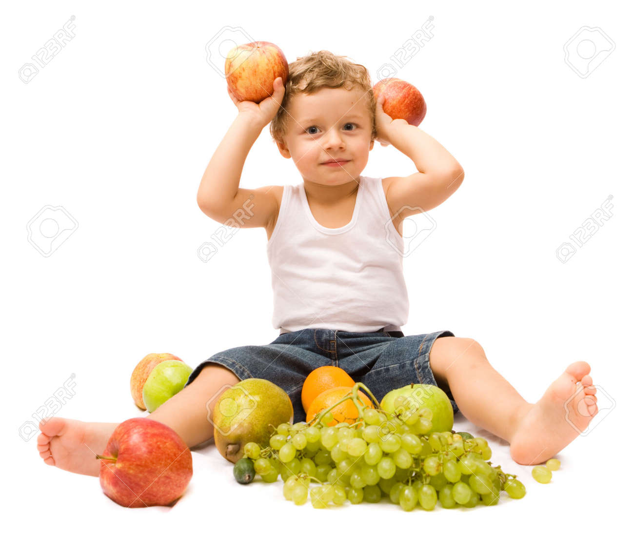 Cute little boy sitting with some fruits. Isolated over white Stock Photo - 3948905