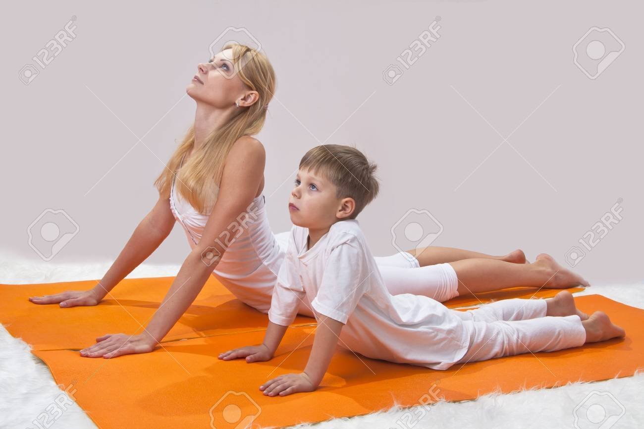 A beautiful young mother practices yoga with her son Stock Photo - 11678763