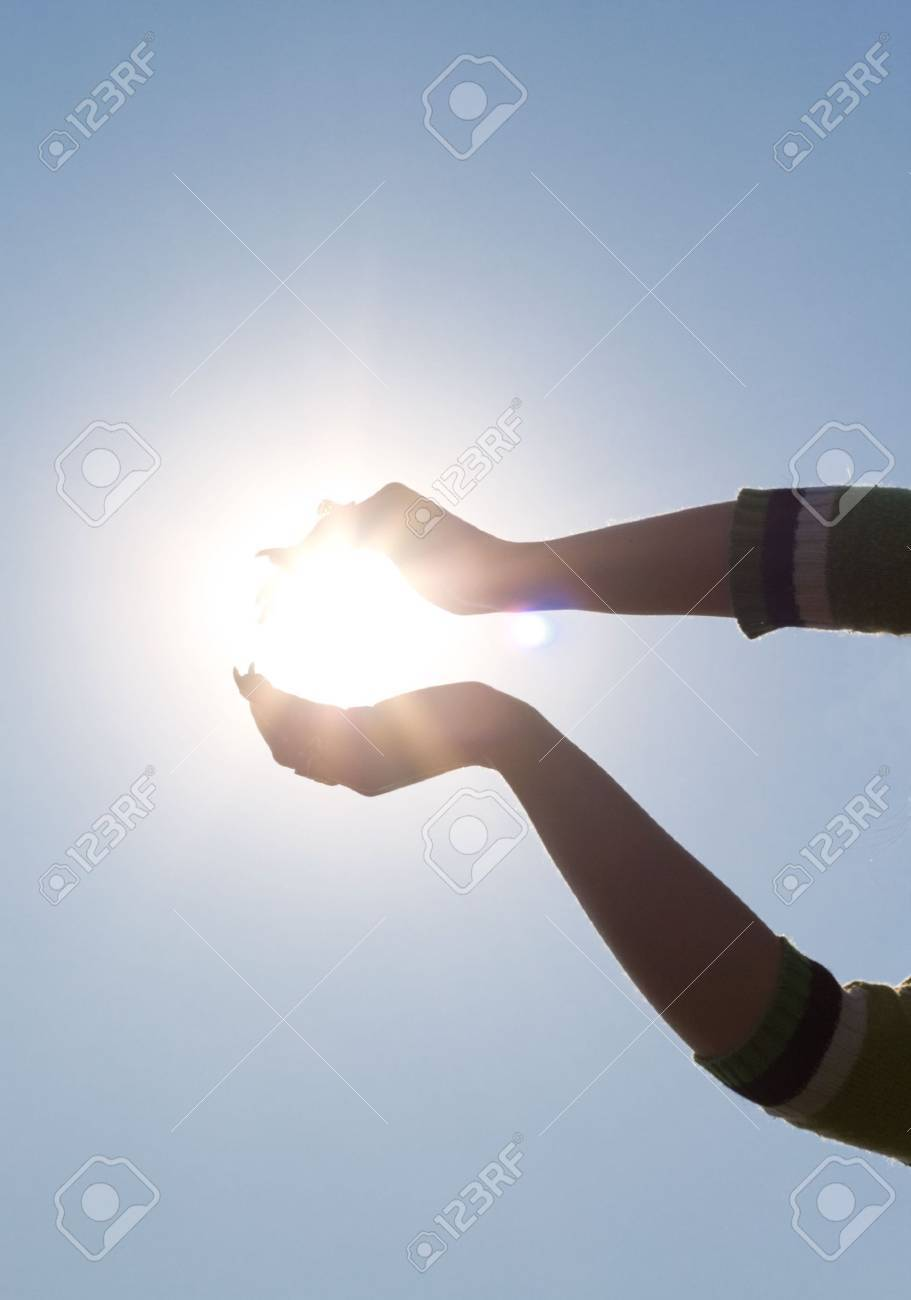 Woman's hands holding sun over blue sky Stock Photo - 4828339