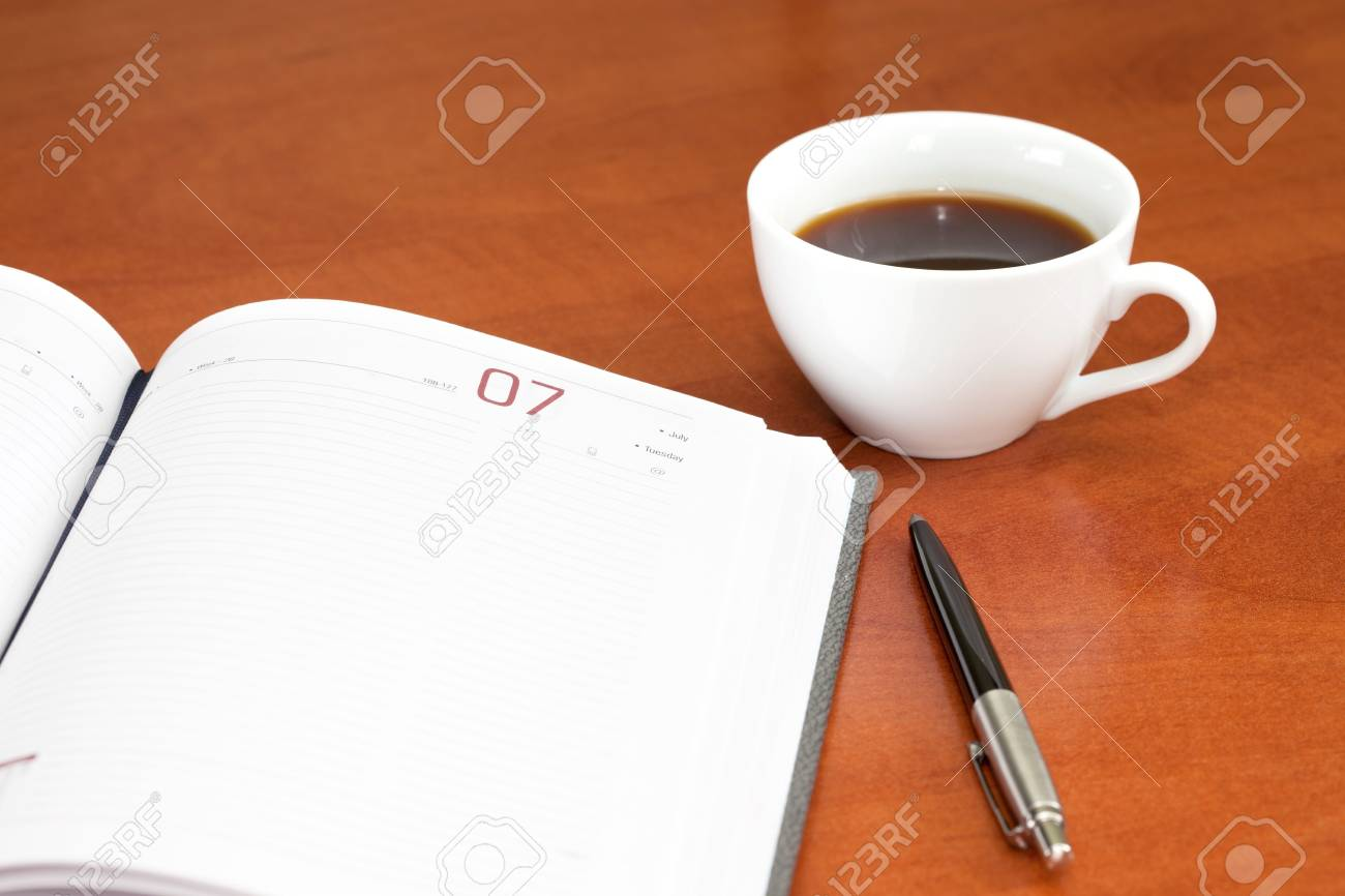 Coffee cup, notebook and pen on the wooden table Stock Photo - 8009267