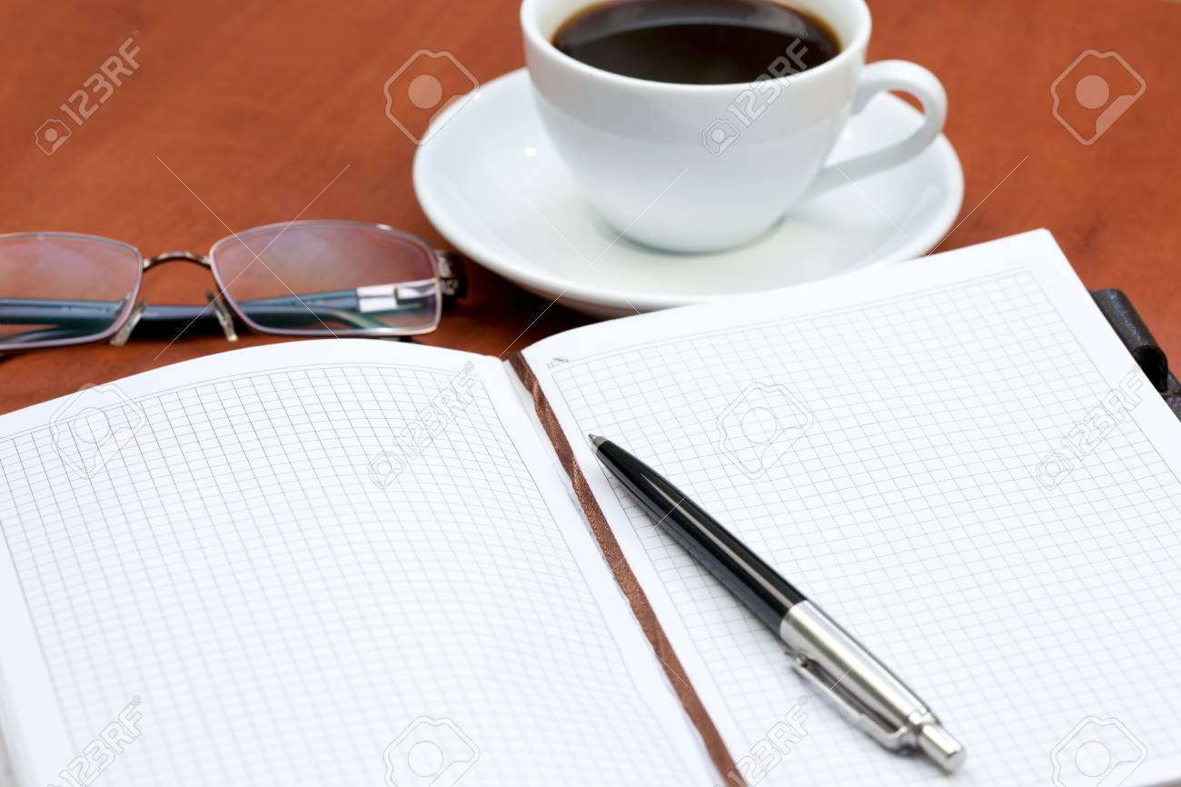 Office table with coffee cup, notebook, pen and glasses Stock Photo - 9252800