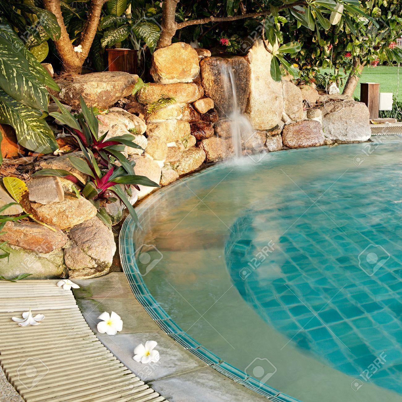 Pool Mit Wasserfall Und Blumen In Einem Resort Lizenzfreie Bilder   10474655