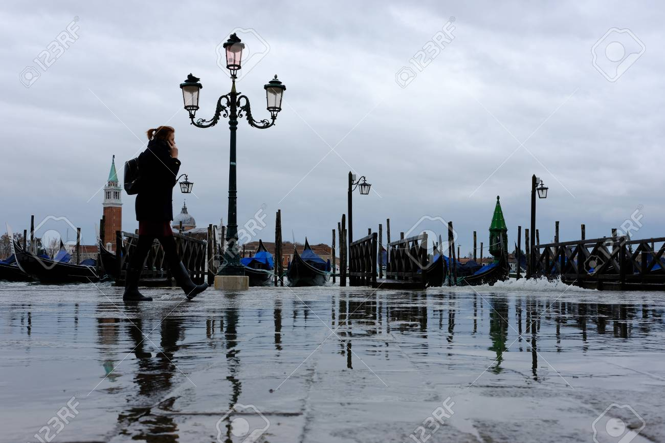 venice, italy november 07, 2017 tourists walking along floodingstock photo venice, italy november 07, 2017 tourists walking along flooding piazza san marco in venice