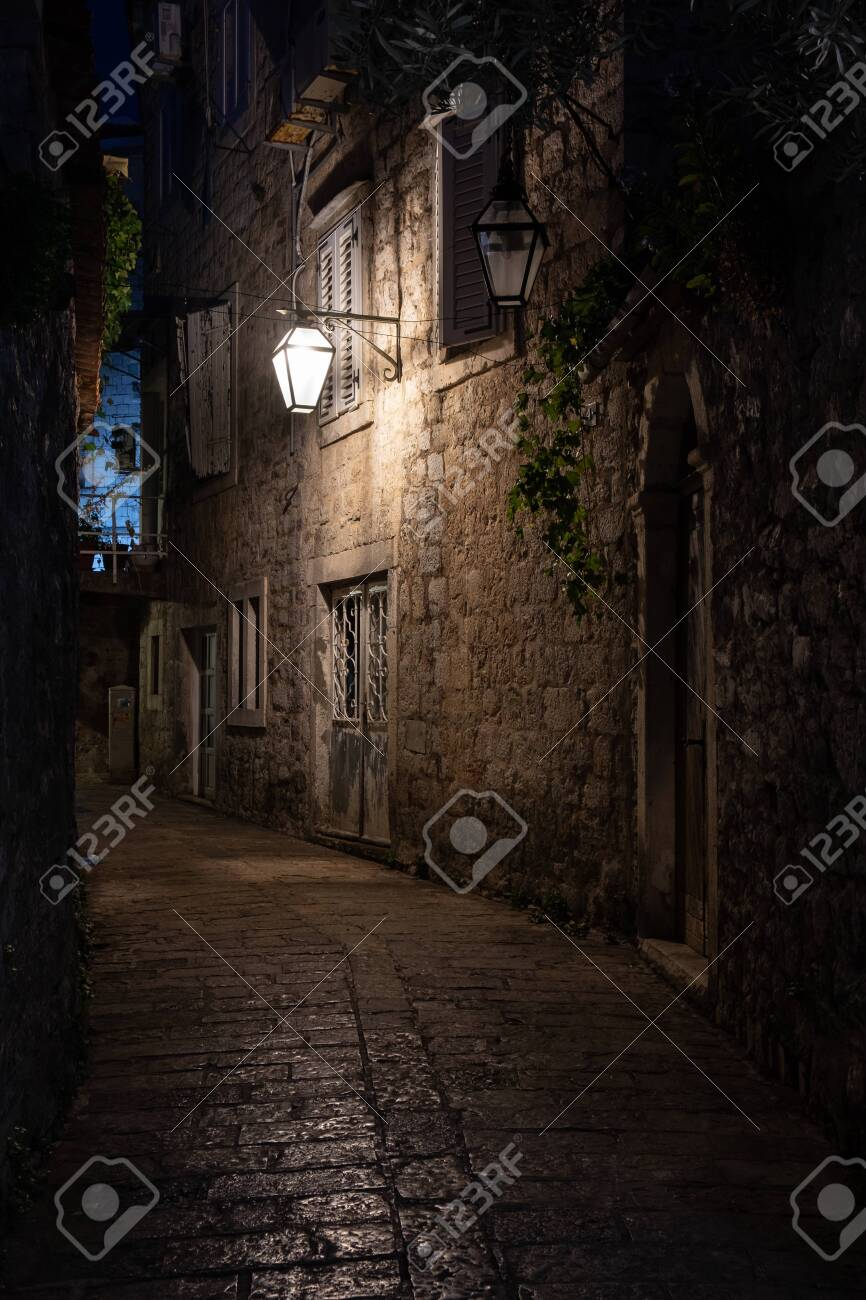 Old street at night illuminated by vintage streetlight. Budva, Montenegro - 120951210