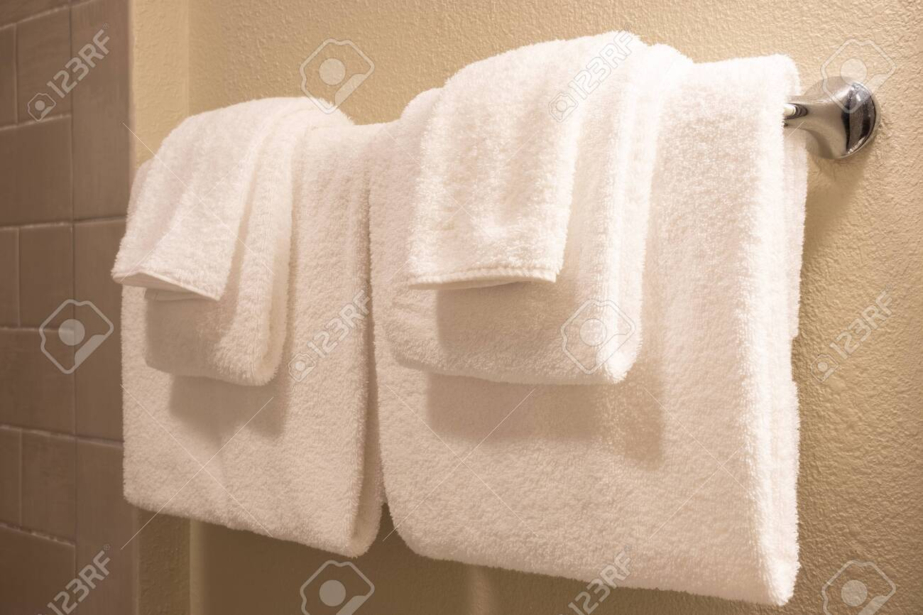 Clean white towel on a hanger prepared to use. - 128316000