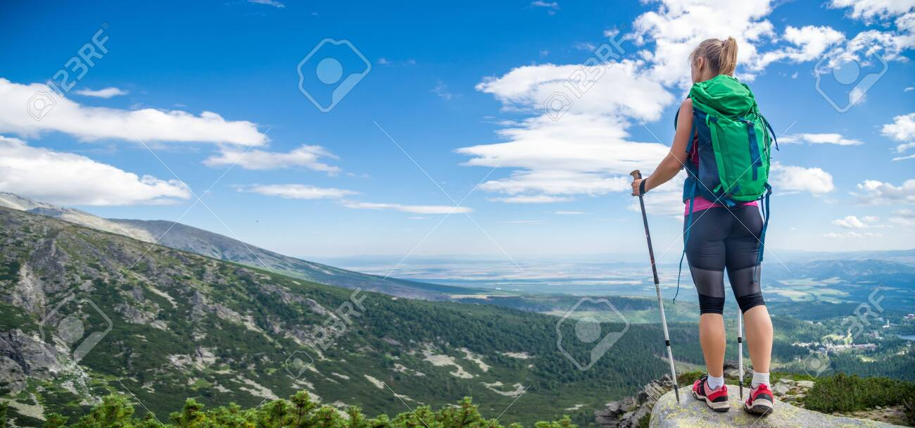 Young woman with backpack hiking in the mountains - 146316924