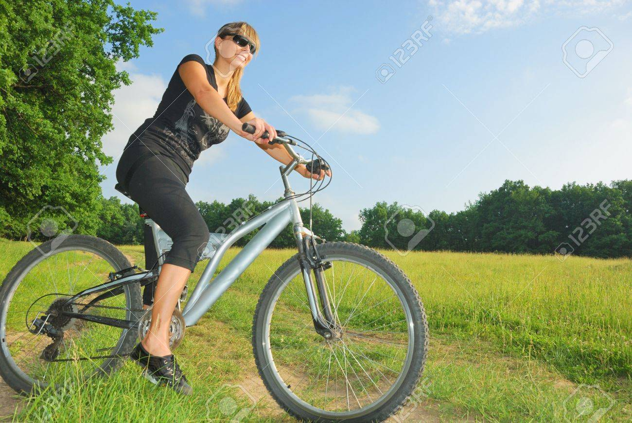 smiling pretty girl riding a bike in green environment Stock Photo - 7307512