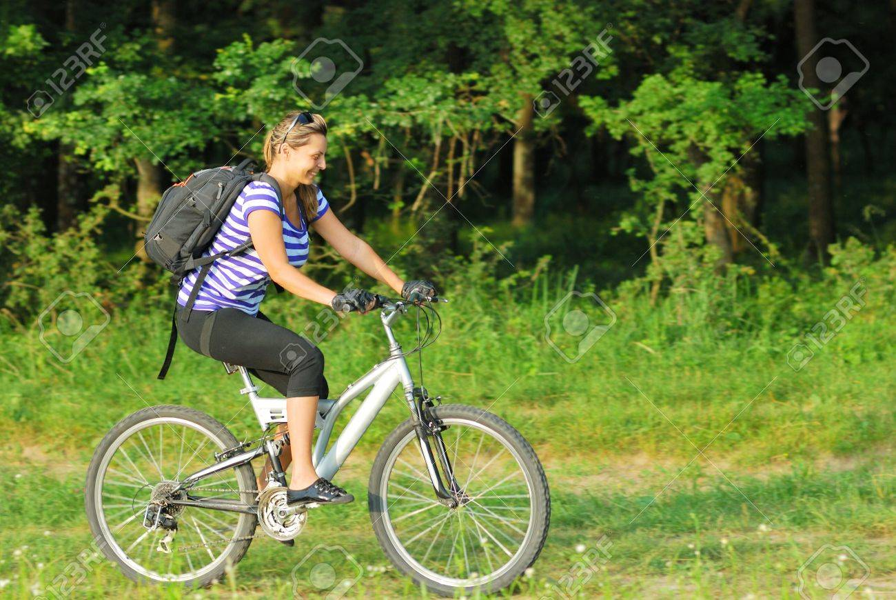 happy blonde young woman traveling on country side with bike Stock Photo - 7352000