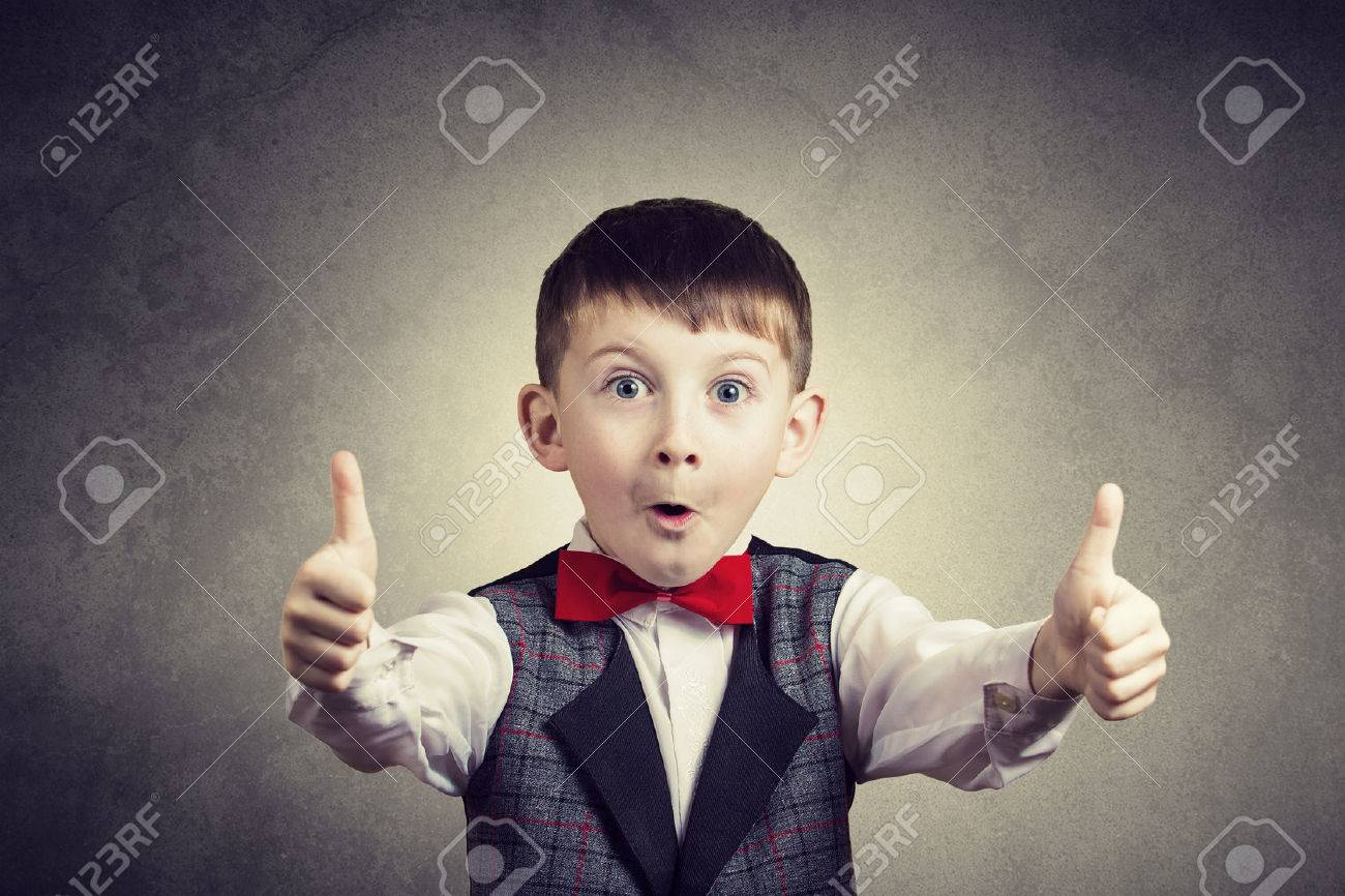 Excited Surprised little boy with thumb up gesture isolated over grey background. - 50460746