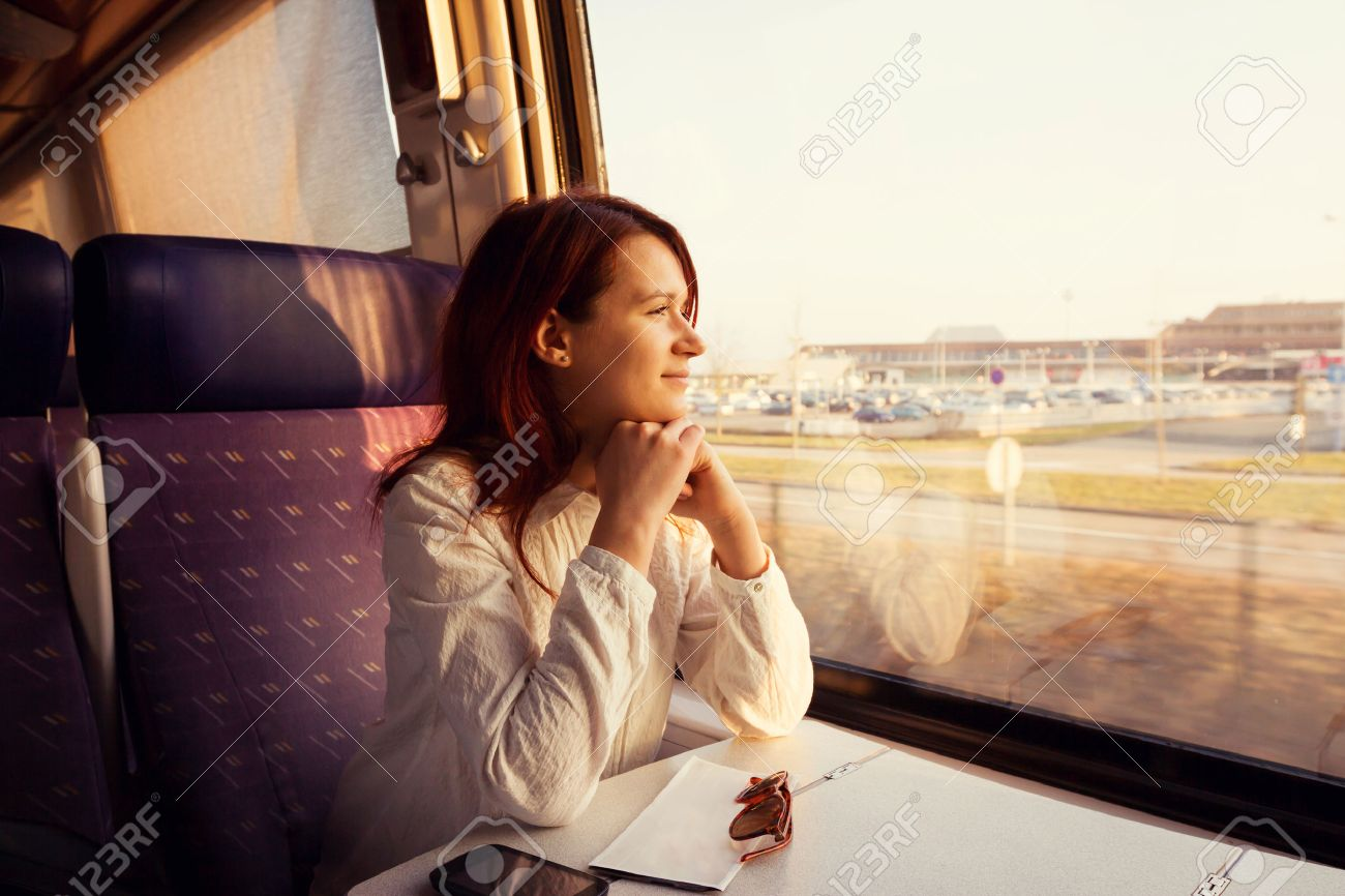 Young woman traveling looking out the window while sitting in the train. - 46324670