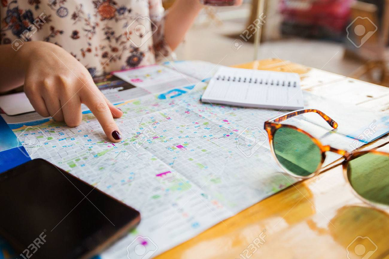stock photo young tourist woman planning a travel trip with a city mapyoung woman making a travel plan for sightseeing the beautiful places of barcelona