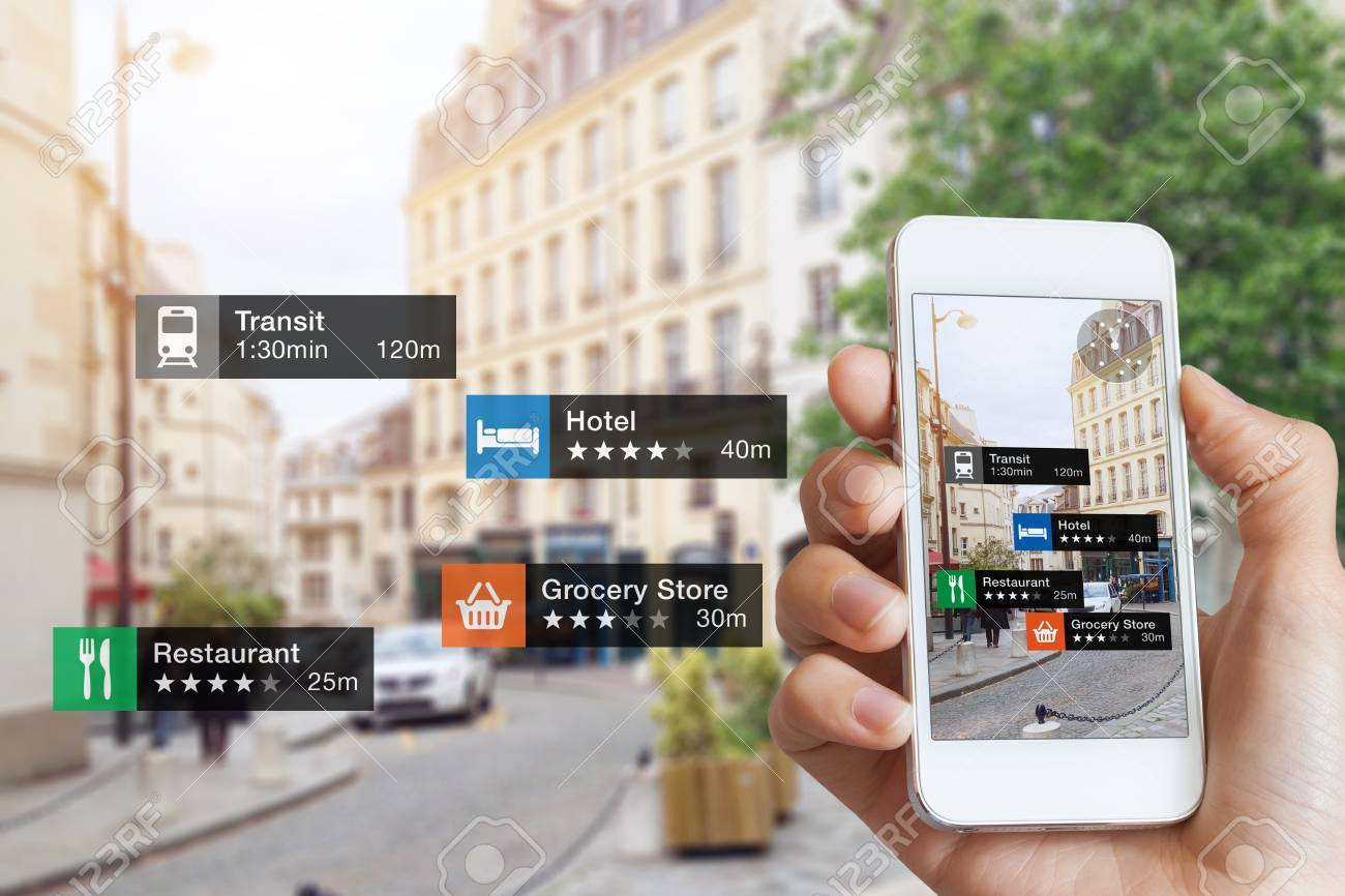 Augmented Reality (AR) information technology about nearby businesses and services on smartphone screen guide customer or tourist in the city, close-up of hand holding mobile phone, blurred street - 90007214