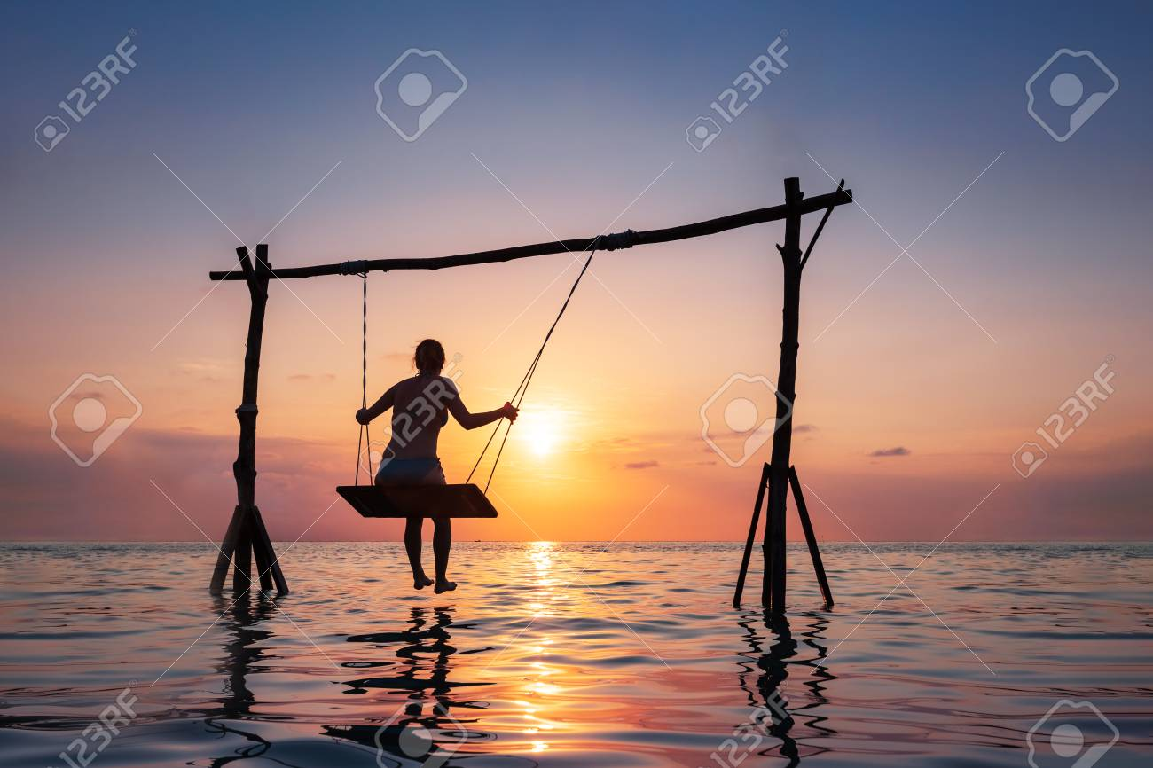 Happy girl relaxing at the beach on rope swing above sea water at sunset, summer vacation holidays resort - 125362951