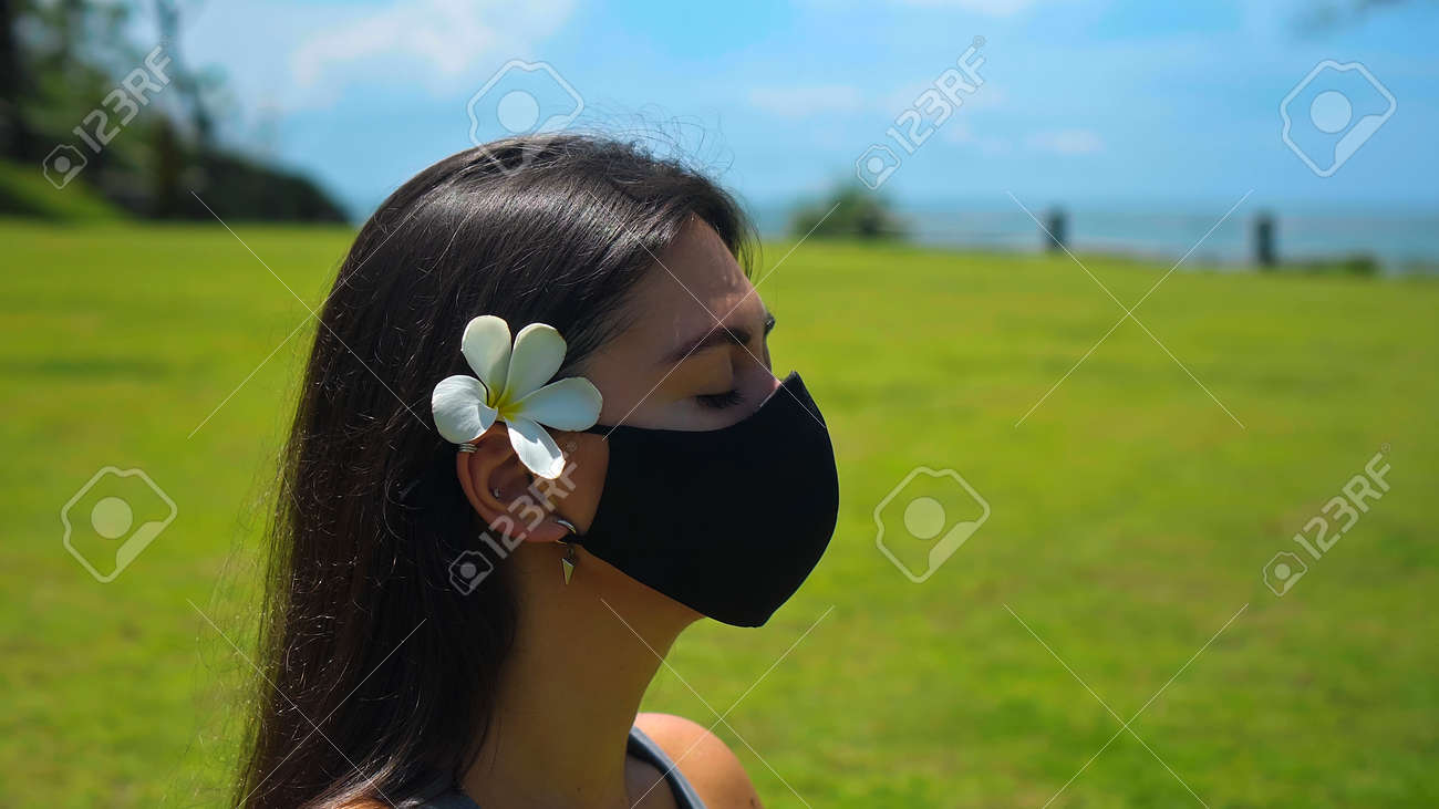 A young European brunette girl practices alone yoga in nature sitting on green grass in a lotus pose wearing a black protective mask on her face and a white flower behind her ear - 170400699