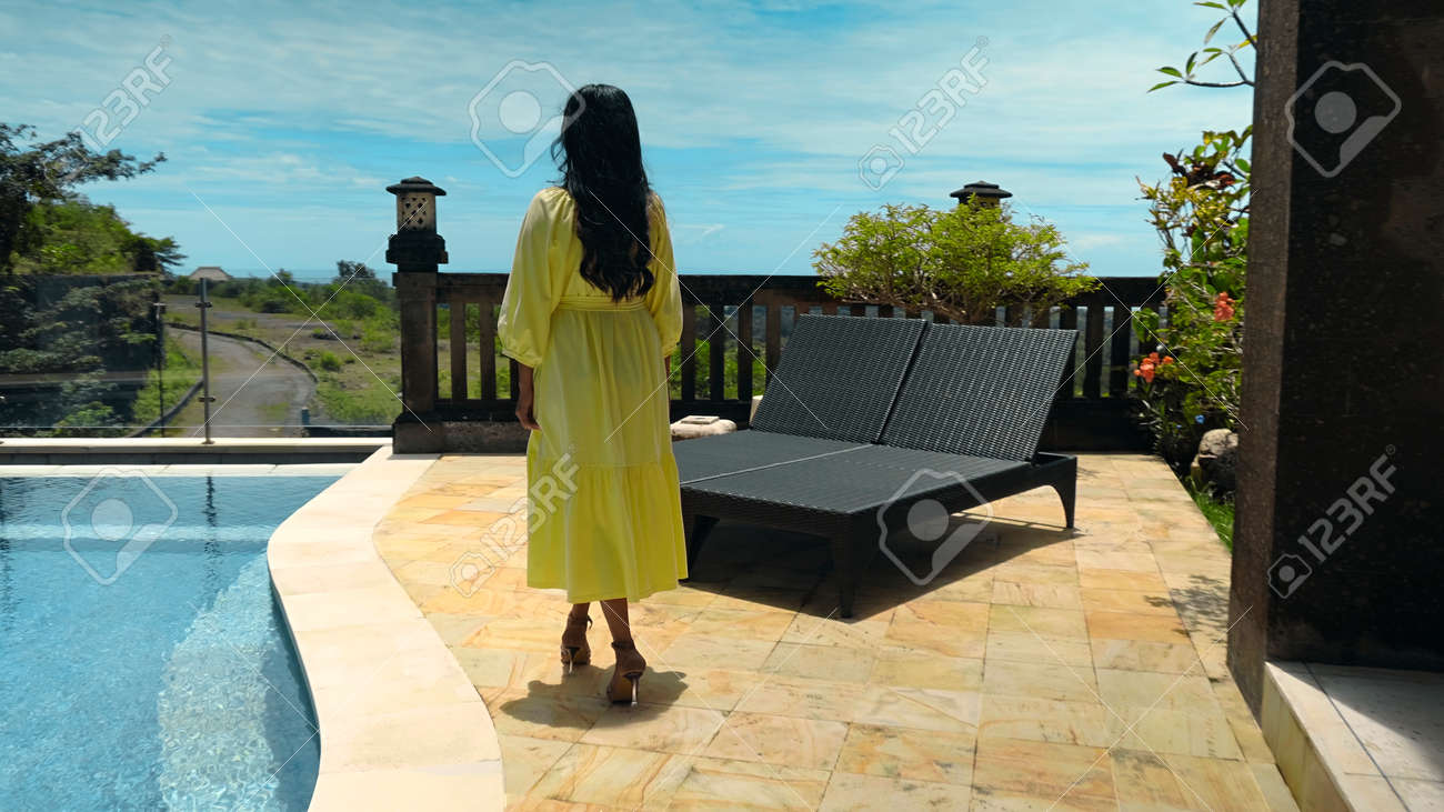 Young long-haired girl walking in the backyard with a green garden, pool with blue clean water and blue sky in a beautiful long yellow dress - 171458558