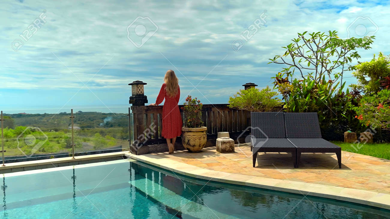 Young long-haired girl walking in the backyard with a green garden, pool with blue clean water and blue sky in a beautiful long red dress - 171458560