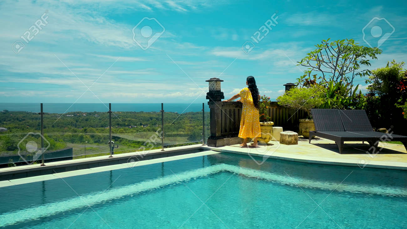Young long-haired girl walking in the backyard with a green garden, pool with blue clean water and blue sky in a beautiful long yellow dress - 171458559