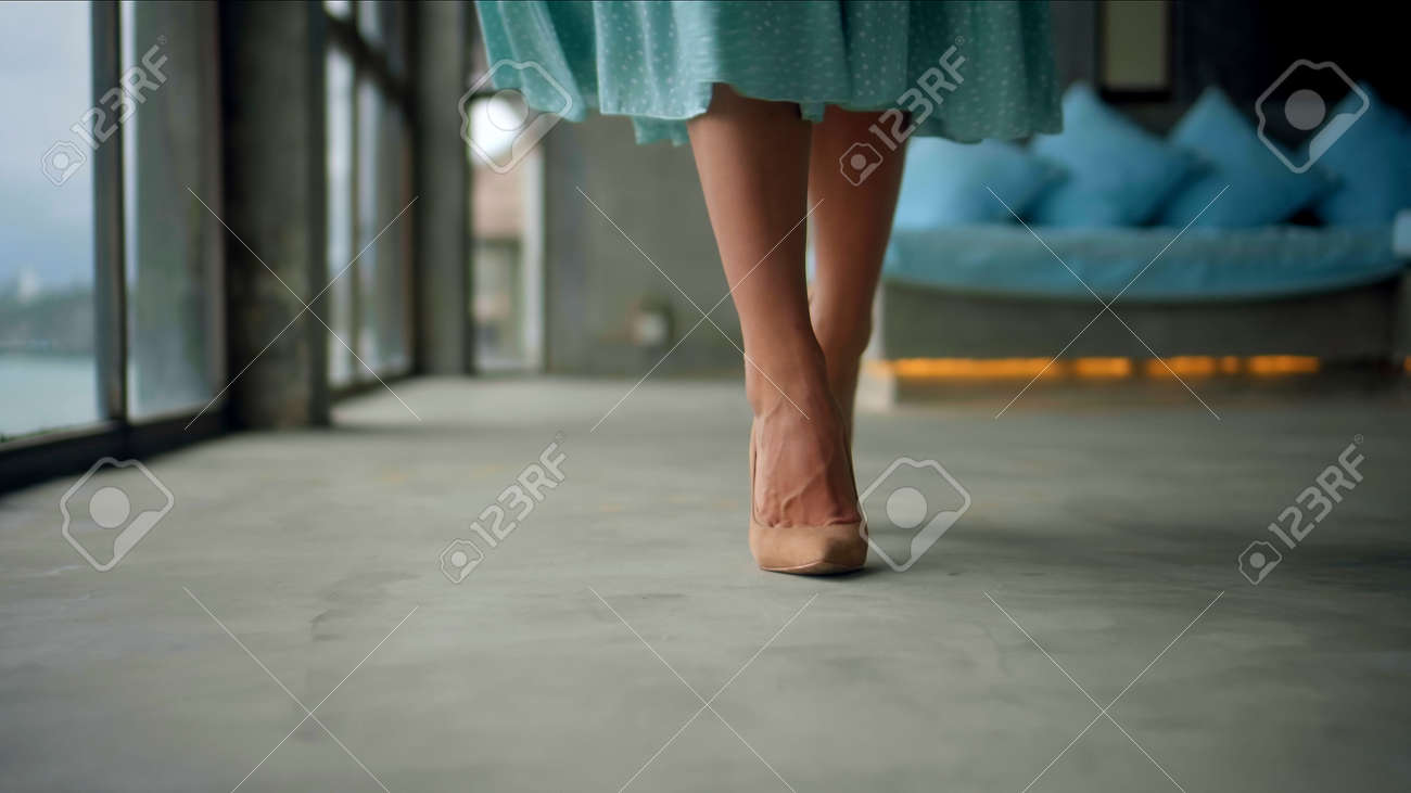The legs of a young and beautiful European girl walking in the room - 169355313