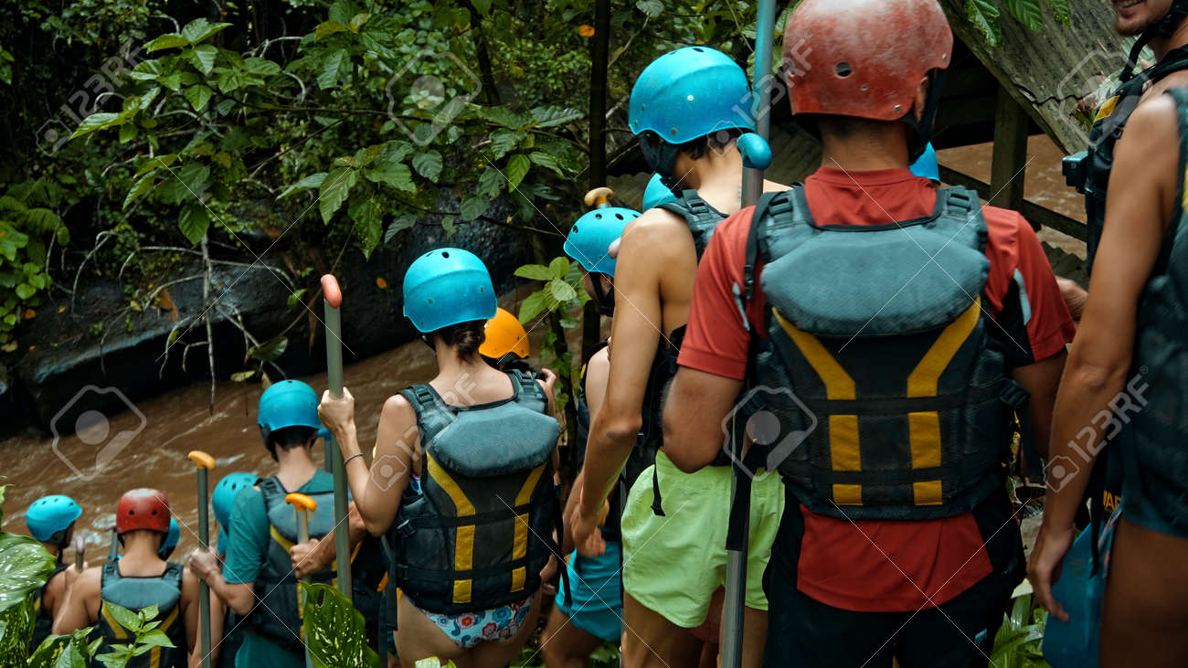 People descending stairs in black protective jackets with yellow lines and protective helmets for rafting and with weights - 171458566