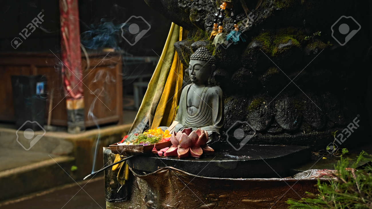 An old stone Budist statue sitting in a lotus pose covered with moss with a wreath of yellow flowers on its neck standing on the street with green plants on the background - 171458567
