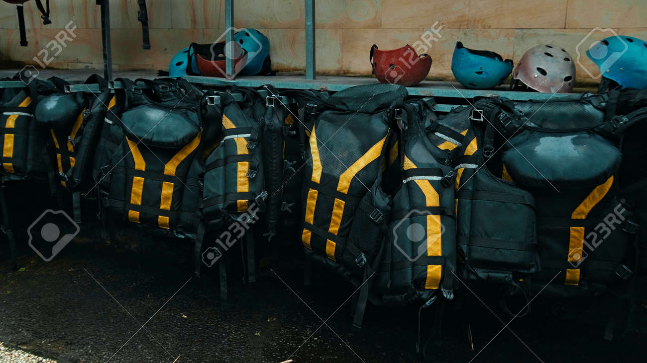 Black protective jackets with yellow lines to practice rafting hanging on a wall on the street - 171028246