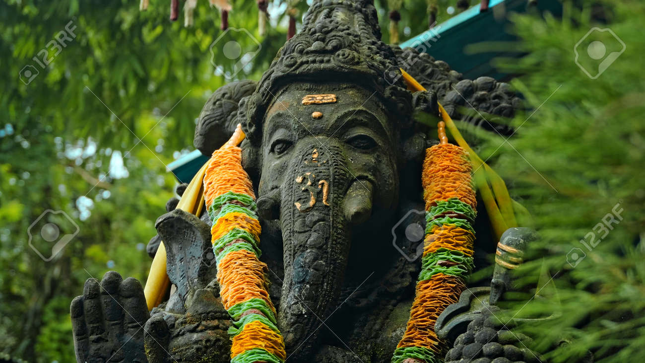 An old stone statue of Ganesha covered with moss with a wreath of yellow flowers on his neck standing on the street with green plants on the background - 171026725