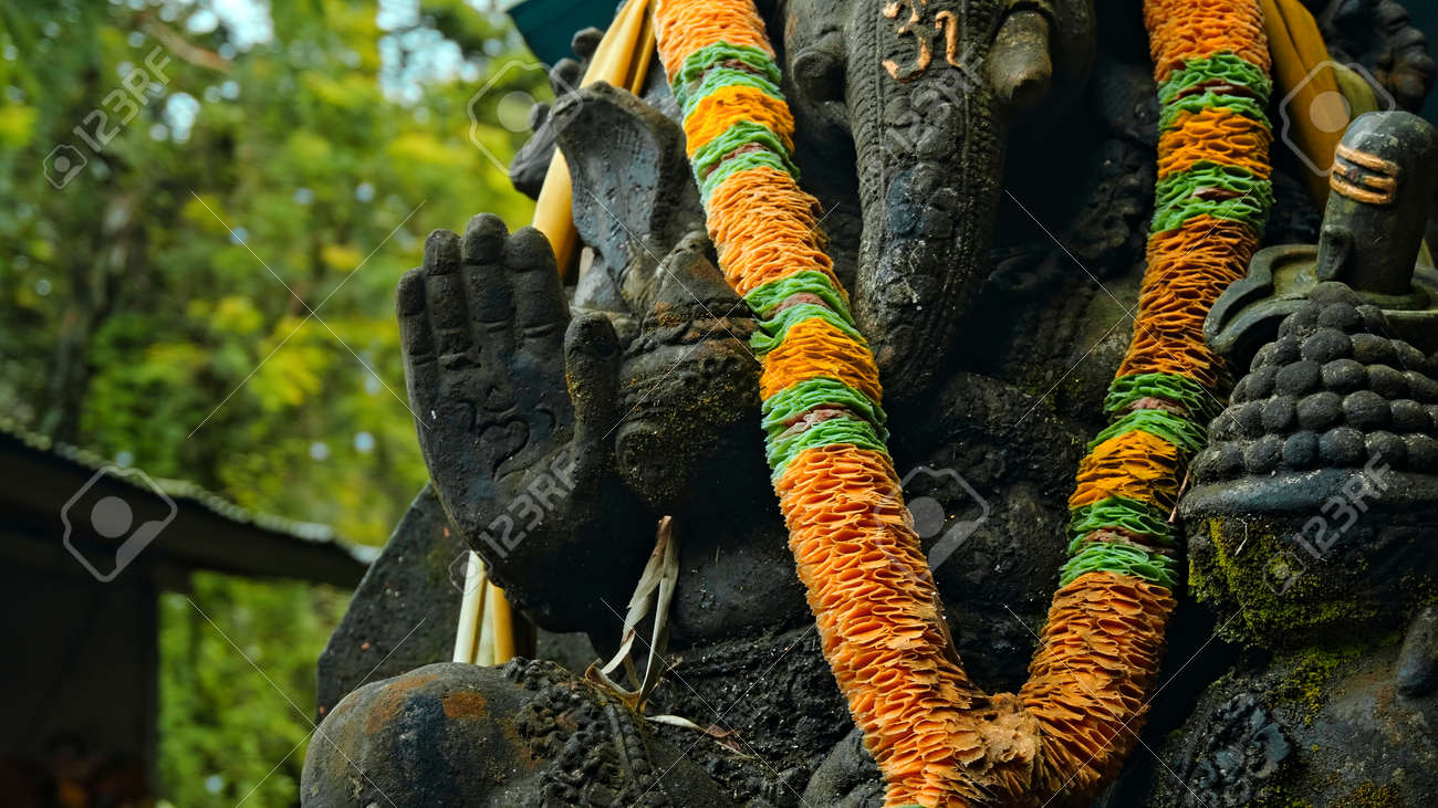 An old stone statue of Ganesha covered with moss with a wreath of yellow flowers on his neck standing on the street with green plants on the background - 171026728