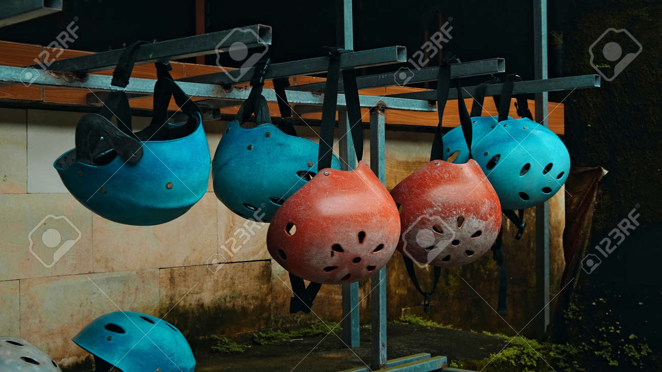 Colored protective helmets for the head to practice rafting hanging on the wall on the street - 171026734