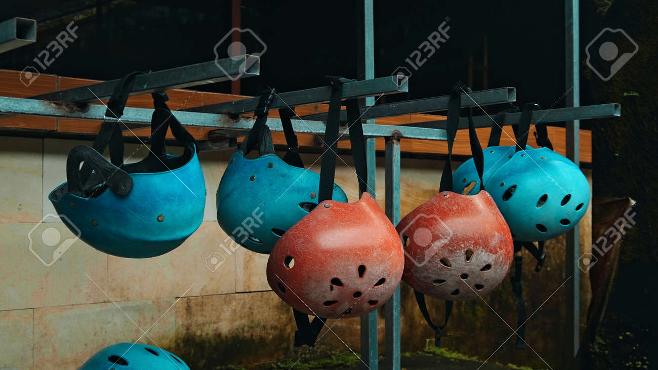 Colored protective helmets for the head to practice rafting hanging on the wall on the street - 171026737