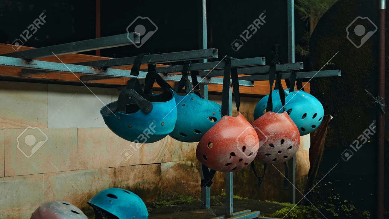 Colored protective helmets for the head to practice rafting hanging on the wall on the street - 171026171