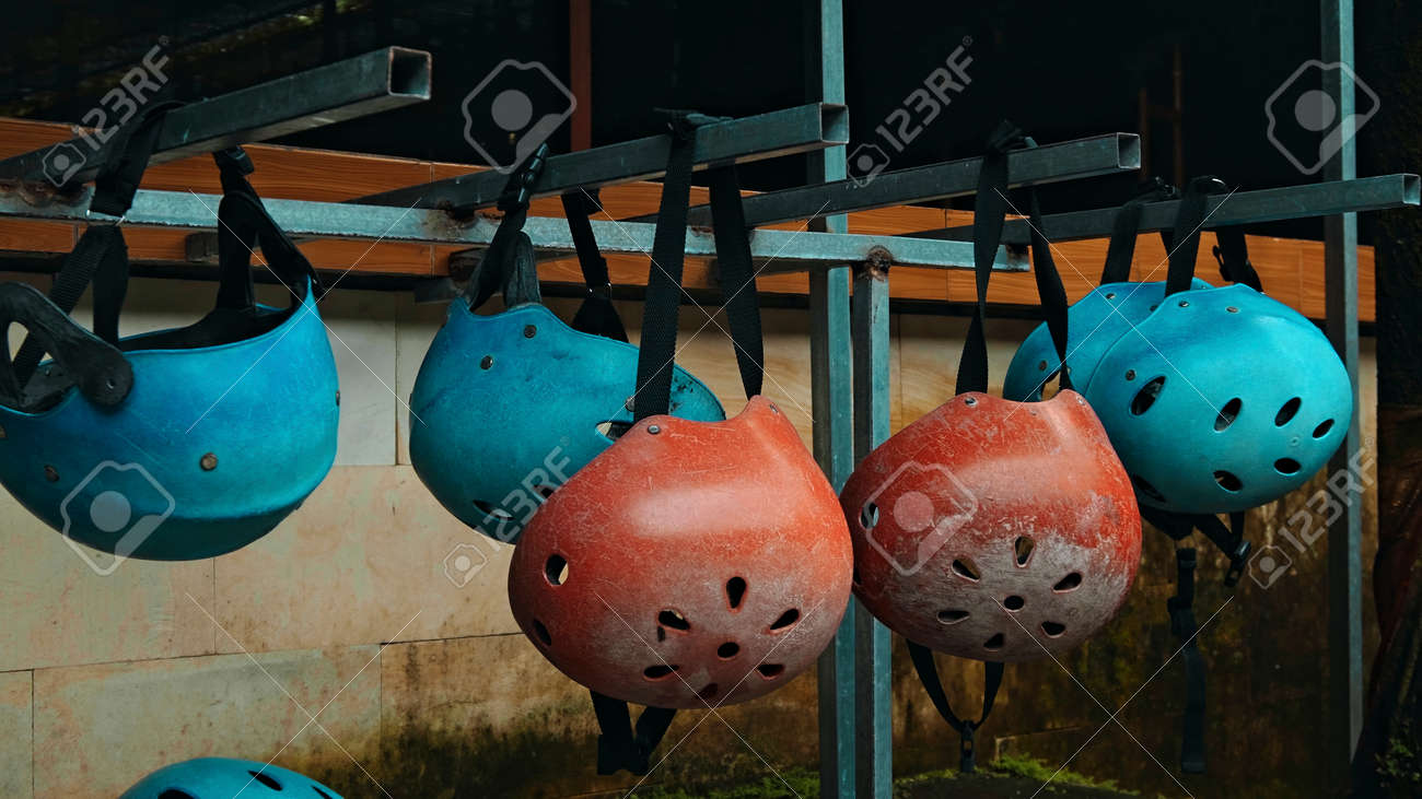 Colored protective helmets for the head to practice rafting hanging on the wall on the street - 171026203