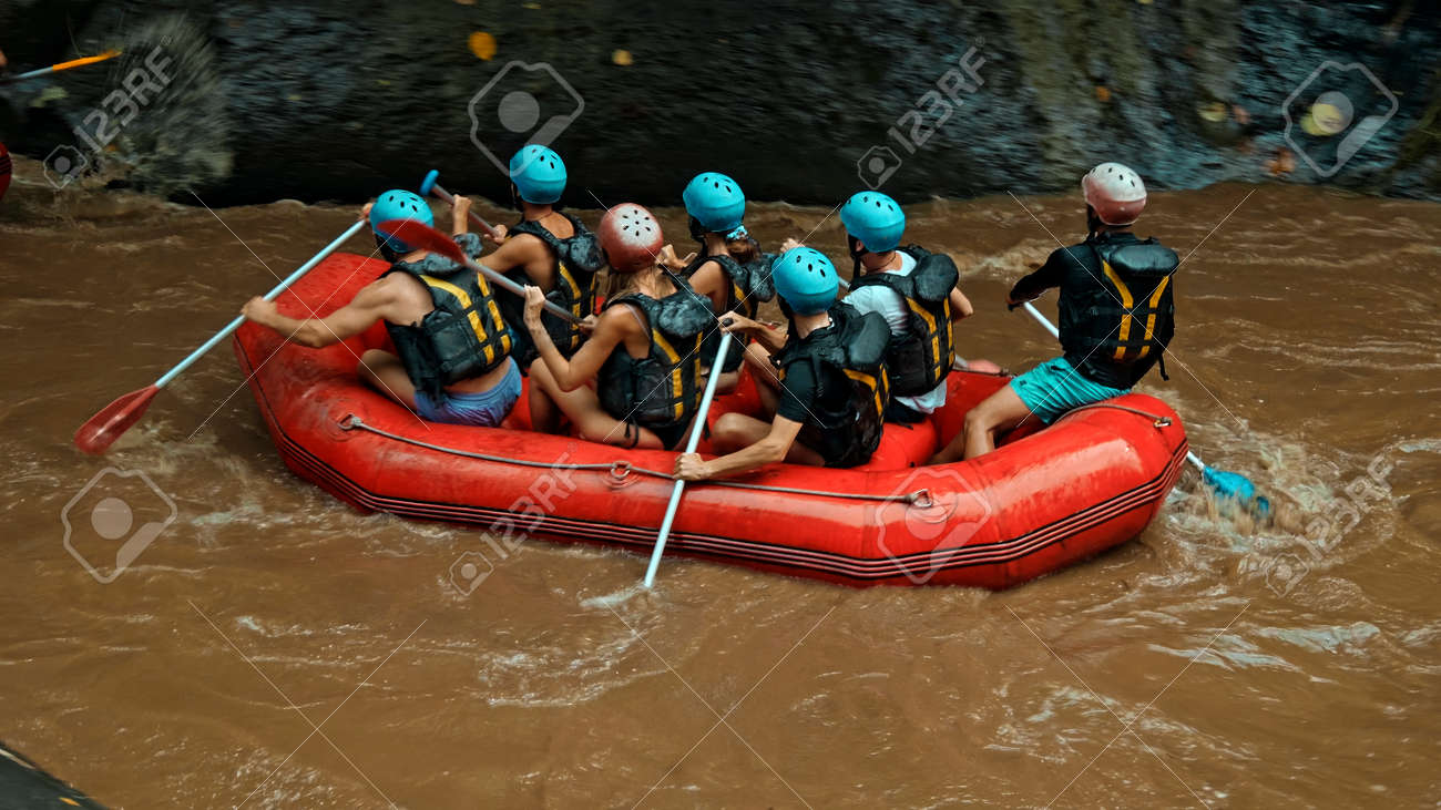 People sailing in black protective jackets with yellow lines and protective helmets on boats for rafting and with weights - 170496877