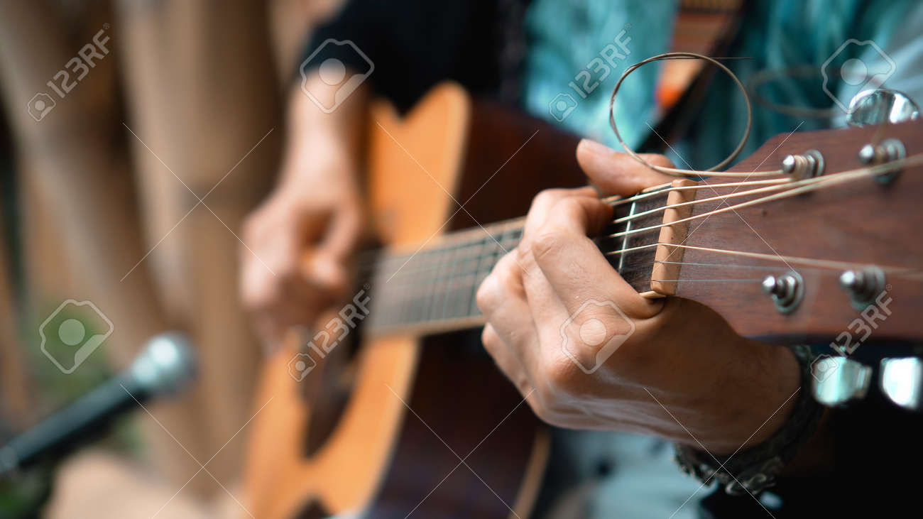 The young man plays hands and on a classic acoustic wooden guitar on the street using a microphone - 171458628