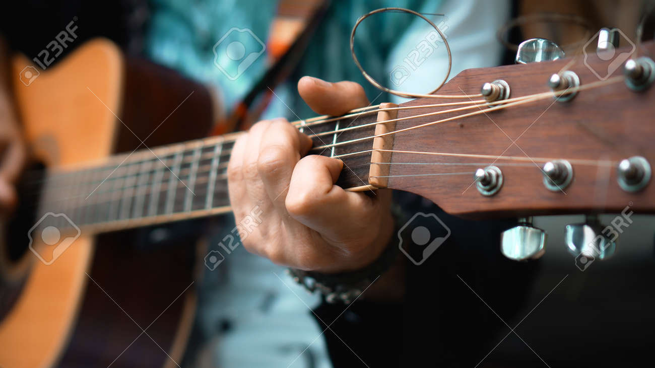 The young man plays hands and on a classic acoustic wooden guitar on the street using a microphone - 170790645