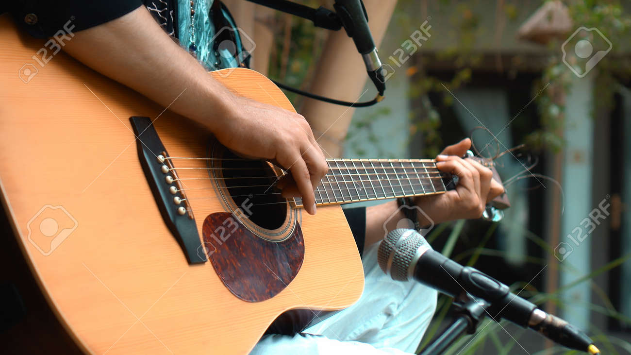 The young man plays hands and on a classic acoustic wooden guitar on the street using a microphone - 170790316