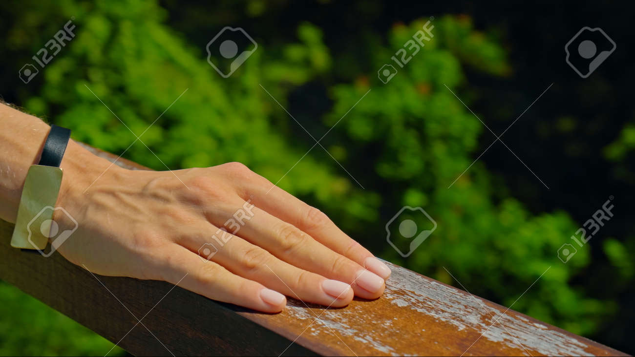A young European girl stands in the summer on a balcony holding her hand to a wooden railing in a green dress - 171458630