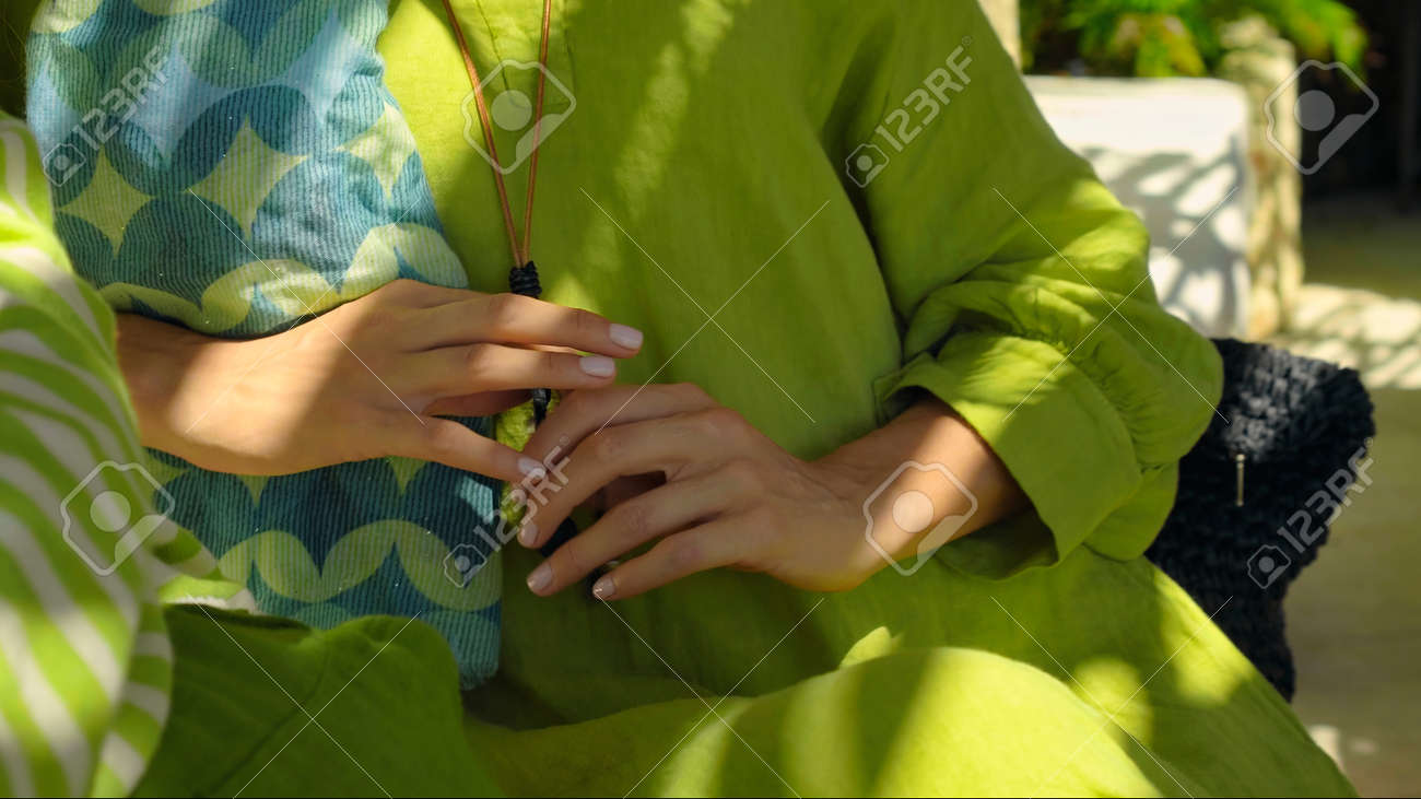 A young girl touches a green dress with her hand sitting on a bench in the backyard - 171458631