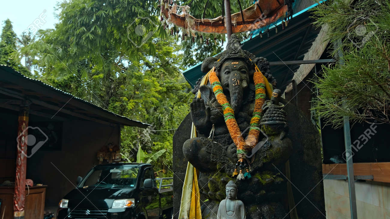 An old stone statue of Ganesha covered with moss with a wreath of yellow flowers on his neck standing on the street with green plants on the background - 171544658