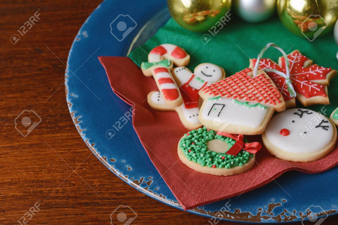 Plate With Colorful Christmas Cookies On Wooden Table