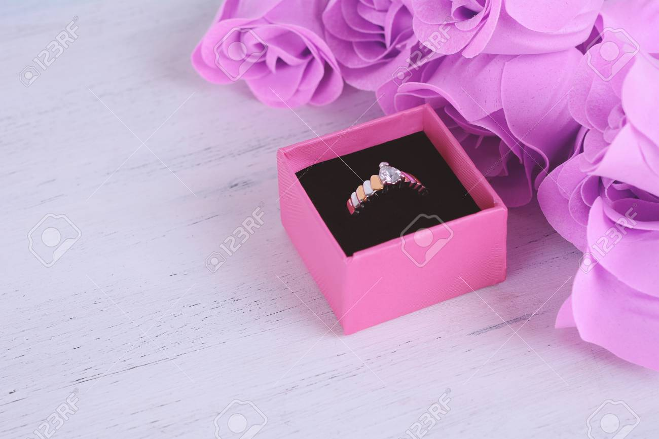 Golden Diamond Ring In Pink Box With Bunch Of Pink Roses On White ...