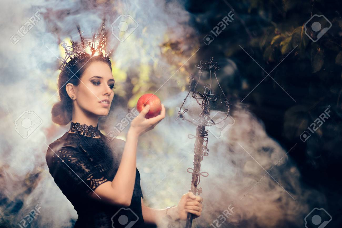 Evil Queen with Poisoned Apple in Misty Forest - 62925379