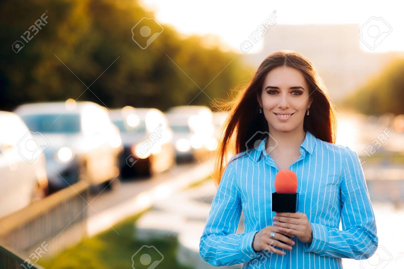 Female News Reporter on Field in Traffic - 78417798